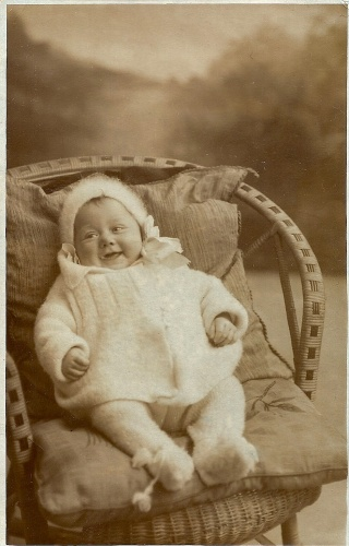 This jolly baby, photographed c.1930, models the latest fashion in hand-knitted novelty woollen pram sets comprising hat, matinée jacket and leggings.