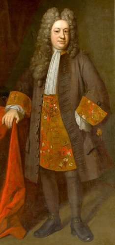 In this painting of 1717, Elihu Yale wears a traditional full-bottomed periwig with built-up peaked crown, expressing late-baroque fashions