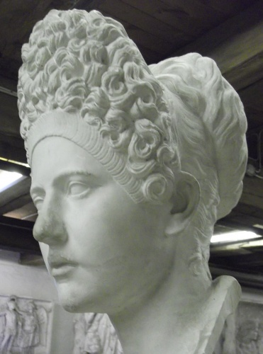 A Roman bust dating from the late 1st century portrays Julia, daughter of the Emperor Titus, wearing a fashionable curled wig expressing her elite status